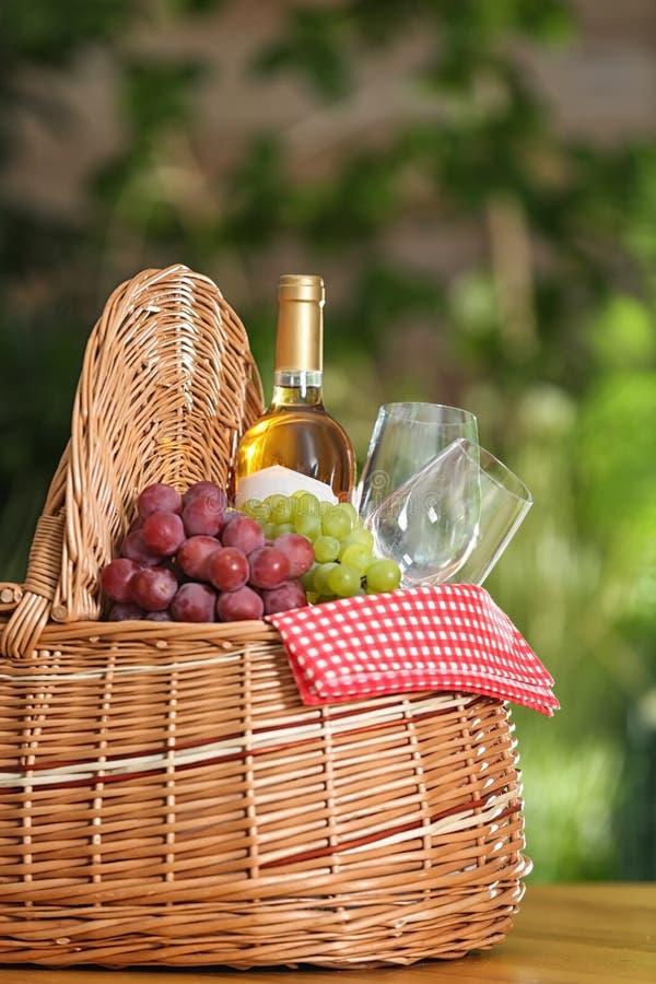 野餐篮子用酒、玻璃和葡萄在木桌上反对被弄脏的背景 免版税图库摄影