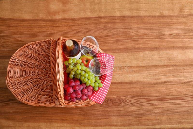 野餐篮子用酒、玻璃和葡萄在木桌上 r 库存照片