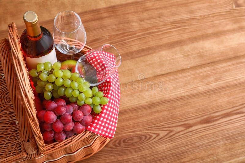 野餐篮子用酒、玻璃和葡萄在木桌上 免版税库存图片