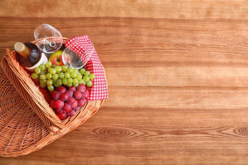 野餐篮子用酒、玻璃和葡萄在木桌,顶视图上 库存图片