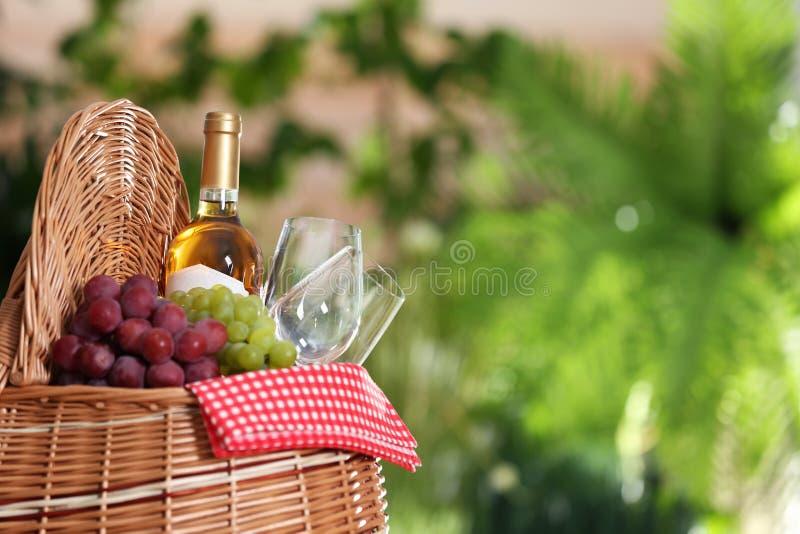野餐篮子用酒、玻璃和葡萄在被弄脏的背景 免版税库存照片