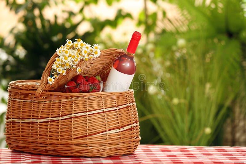野餐篮子用酒、草莓和花在方格的桌布反对被弄脏的背景 免版税库存照片