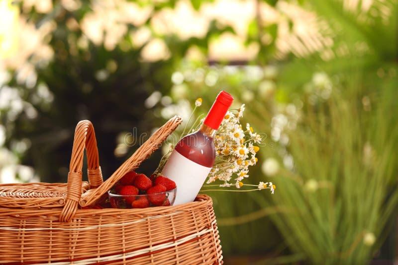 野餐篮子用酒、草莓和花在被弄脏的背景 库存照片