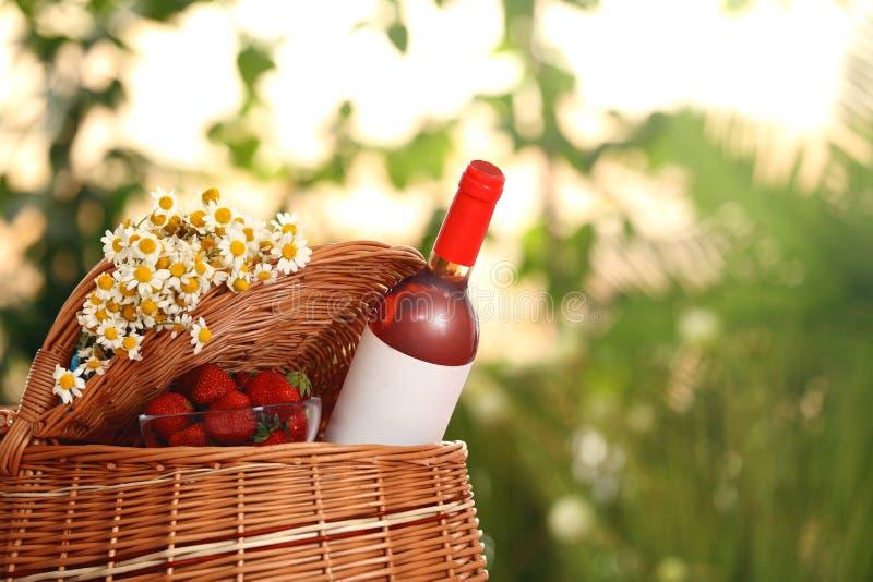 野餐篮子用酒、草莓和花在被弄脏的背景 库存图片
