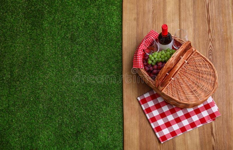 野餐篮子用酒和葡萄在木表面室外,顶视图 免版税图库摄影