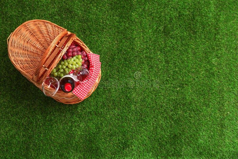 野餐篮子用酒和葡萄在草 r 免版税库存照片