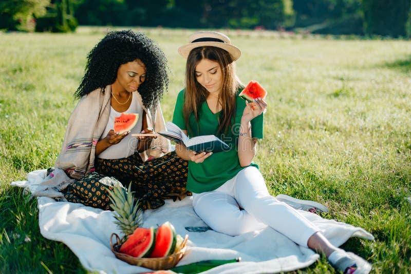野餐题材 可爱的非洲女孩吃着西瓜并且通过手机聊天,当她引诱时 免版税库存图片