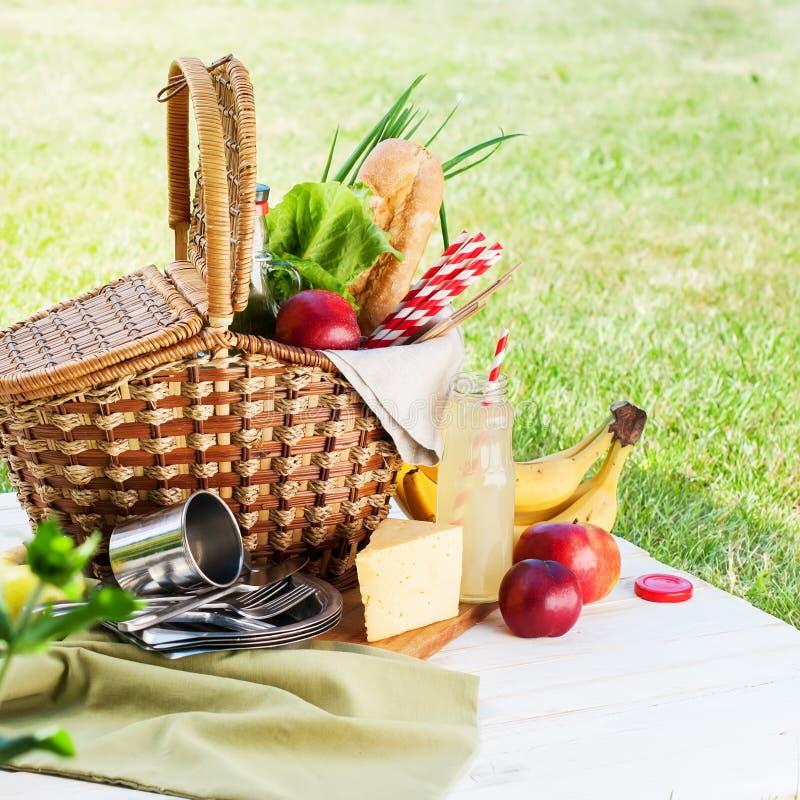 野餐Wattled篮子设置食物面包饮料 免版税库存照片