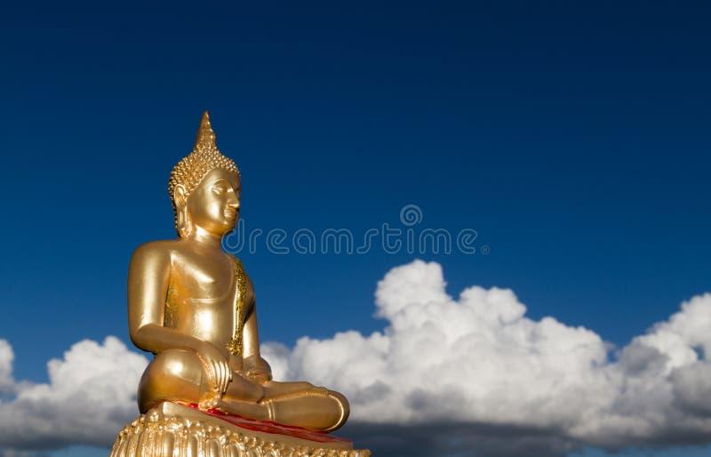 金与蓝色多云天空的菩萨雕象 免版税库存照片