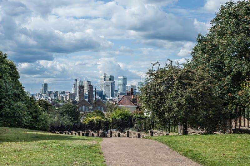 金丝雀码头在伦敦在从格林威治公园看见的剧烈的天空下 库存照片