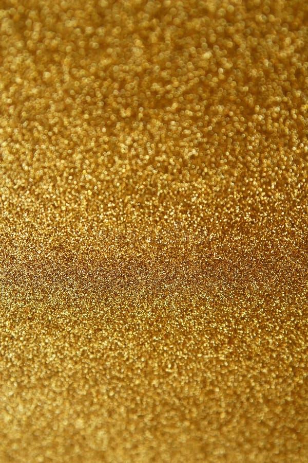 金光纹理闪光纸背景 摘要闪烁的金色闪光背景,带有波光、散焦光 免版税库存照片