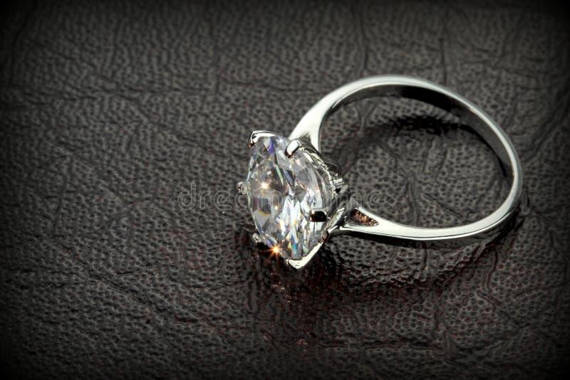 金刚石在黑皮革背景的单粒宝石圆环 免版税库存图片