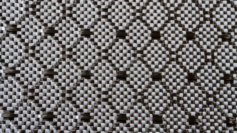 金刚石看法的被编织的黑碳纤维合成材料背景关闭 免版税库存照片