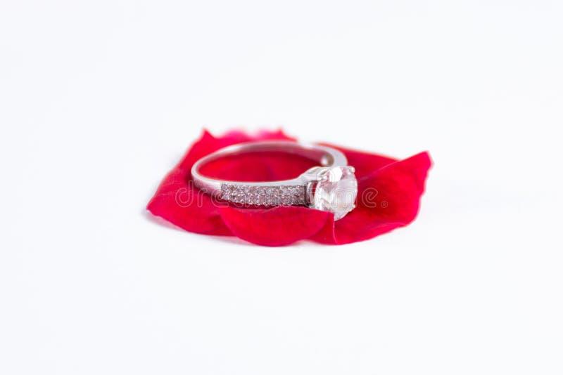 金刚石订婚在白色隔绝的红色玫瑰花瓣的婚戒 图库摄影
