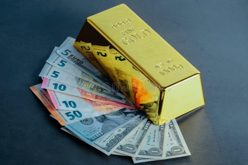 金制马上的齿龈以美元和欧元票据为背景的锭金块 免版税库存照片
