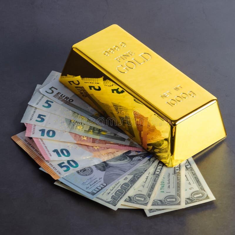 金制马上的齿龈以美元和欧元票据为背景的锭金块 库存照片