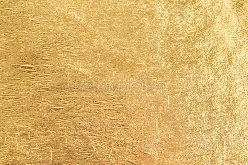 金发光的箔背景,黄色光泽金属纹理 免版税库存照片