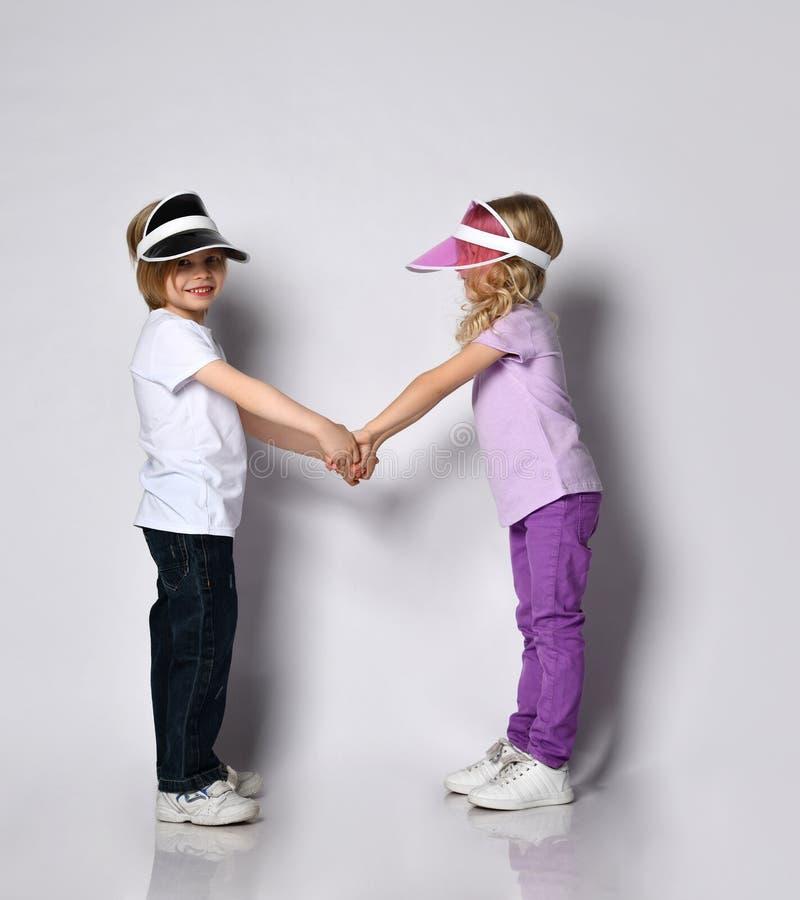 金发小女孩,穿着五颜六色的休闲服和遮阳衣 笑着,相望着对方,在白色上孤立地摆着 免版税图库摄影