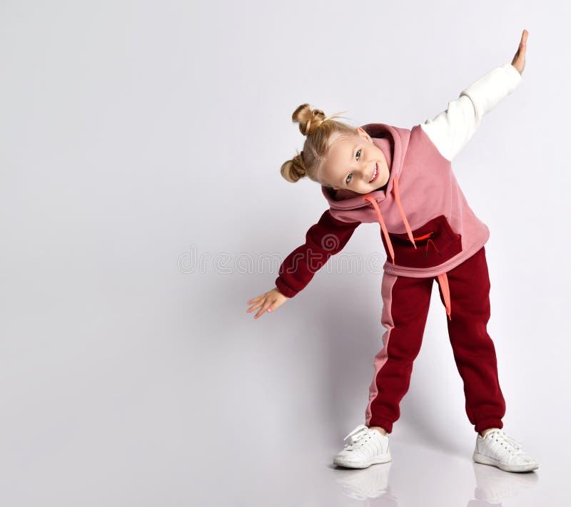 金发小孩,发型丰满,穿着五颜六色的运动服,运动鞋 微笑,表演运动,在白色上孤立 免版税库存图片