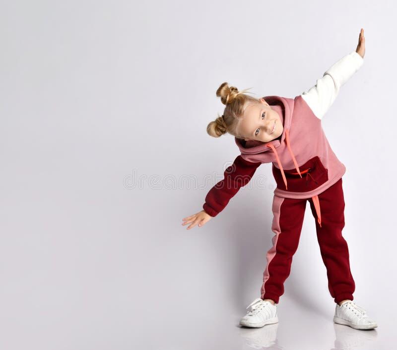 金发小孩,发型丰满,穿着五颜六色的运动服,运动鞋 微笑,表演运动,在白色上孤立 免版税库存照片