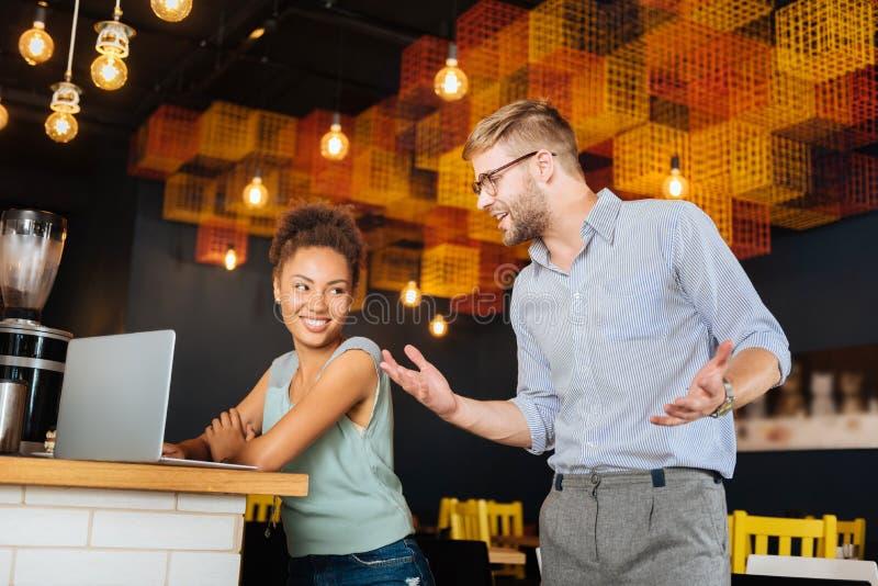 金发的人佩带的玻璃谈话与他的同事 图库摄影
