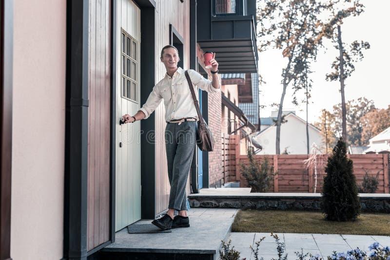 金发的人用外带的咖啡谈话与他的邻居早晨 库存照片