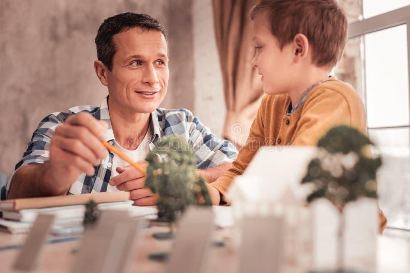 金发的养子询问他的父亲关于树 免版税库存图片