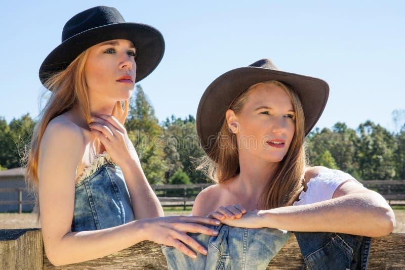 年轻金发碧眼的女人和成熟女性黑帽会议门画象的 免版税库存图片