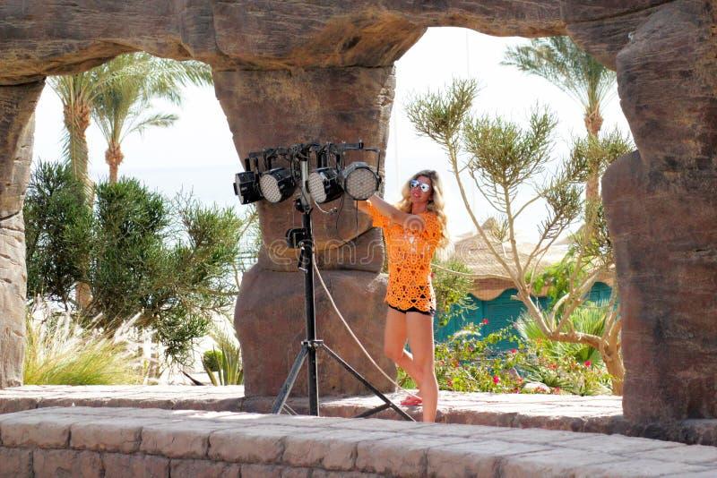 金发碧眼的女人太阳镜的和在聚光灯附近的橙色衣裳的在晴朗的天气的露天舞台 免版税图库摄影