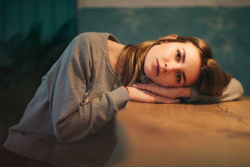 金发碧眼的女人画象有长发的,头在桌上说谎 图库摄影