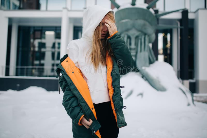 金发碧眼的女人的图片敞篷和夹克的反对大厦背景  免版税库存照片