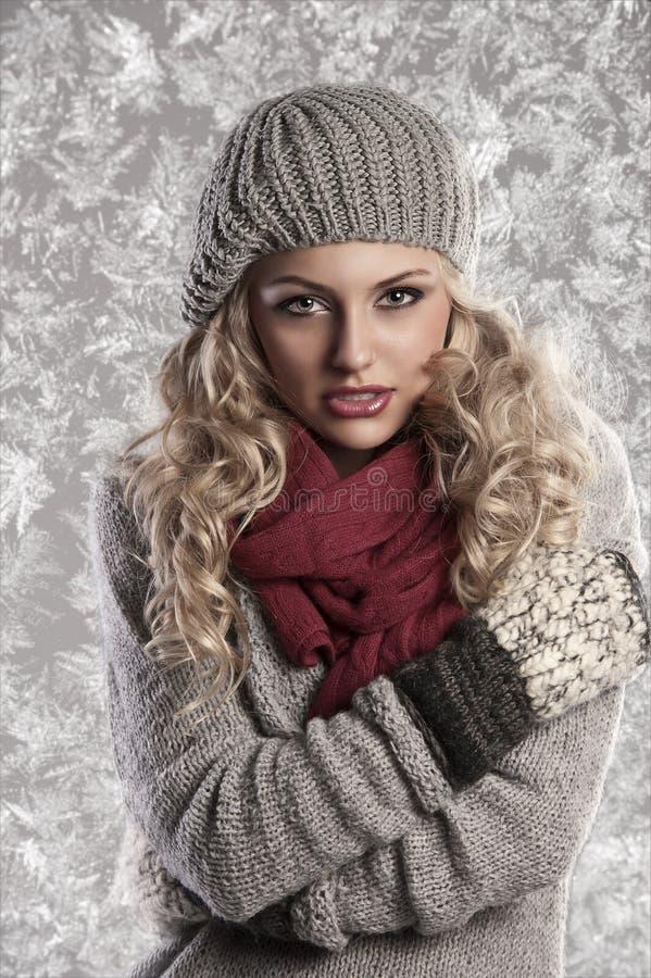 金发碧眼的女人给女孩冬天美妙羊毛&# 图库摄影