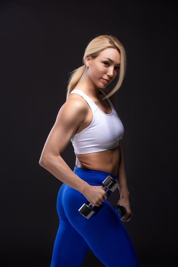 金发美女,戴着哑铃和肌肉姿势 库存图片