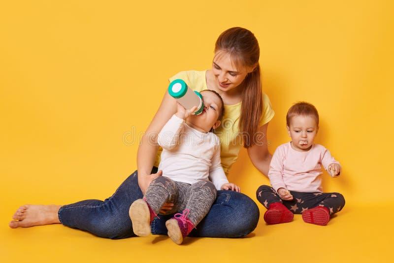 金发,爱恋的母亲照看她的小服从的孩子,有膳食,在妈妈的腿和坐与嘴的地板 库存图片