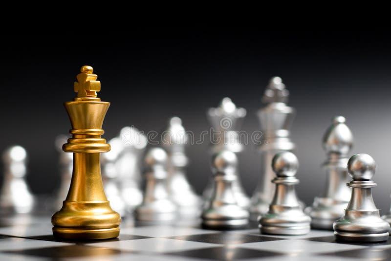 金国王与另一个银色队的棋子面孔在黑背景 免版税库存图片