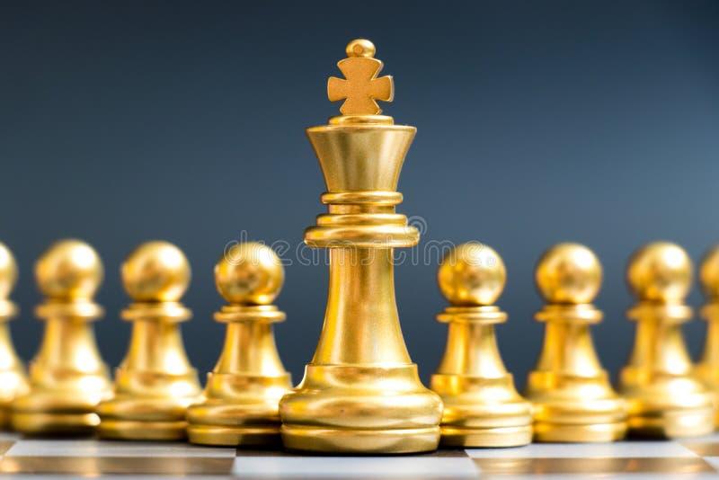 金国王在典当前面的棋子立场在黑背景 库存图片