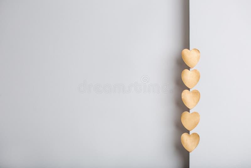 金在灰色织地不很细背景的心脏贴纸 库存图片