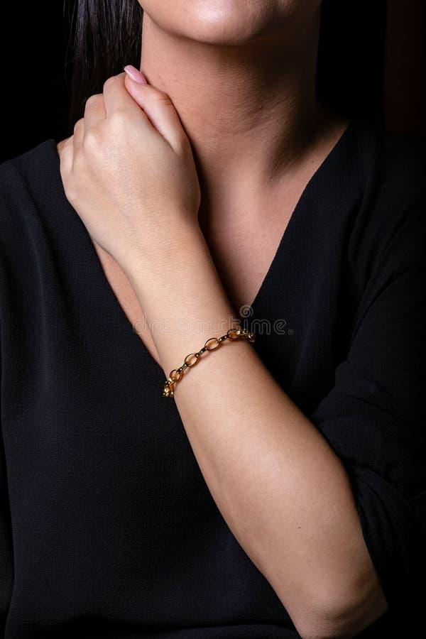 金女性镯子在手边以在黑背景互联的长圆形的形式 免版税库存照片
