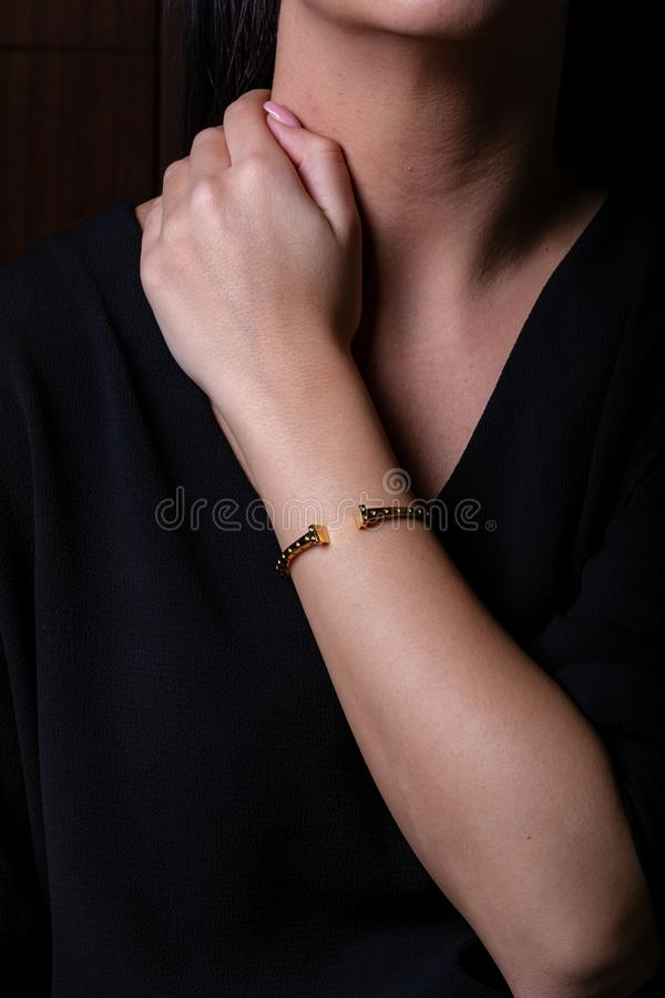 金女性镯子在手边有两个正方形的在最后在黑背景 免版税图库摄影