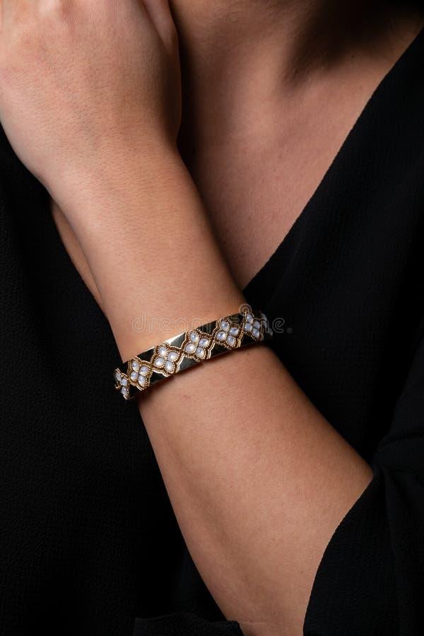 金女性镯子在手边有花石头和形状的在黑背景的 免版税库存照片
