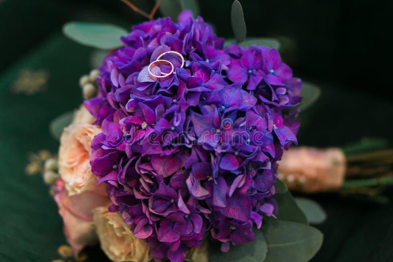 金婚在紫色八仙花属,与淡紫色丝带的桃红色玫瑰花花束敲响在土气样式 库存照片