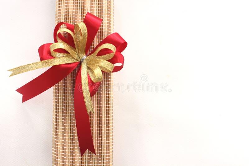 金子和红色丝带鞠躬与在白色背景的giftbox 库存图片