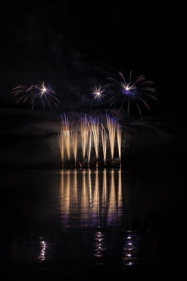 金子和蓝色喷泉在富有的烟花在布尔诺的水坝表面有湖反射的 库存照片