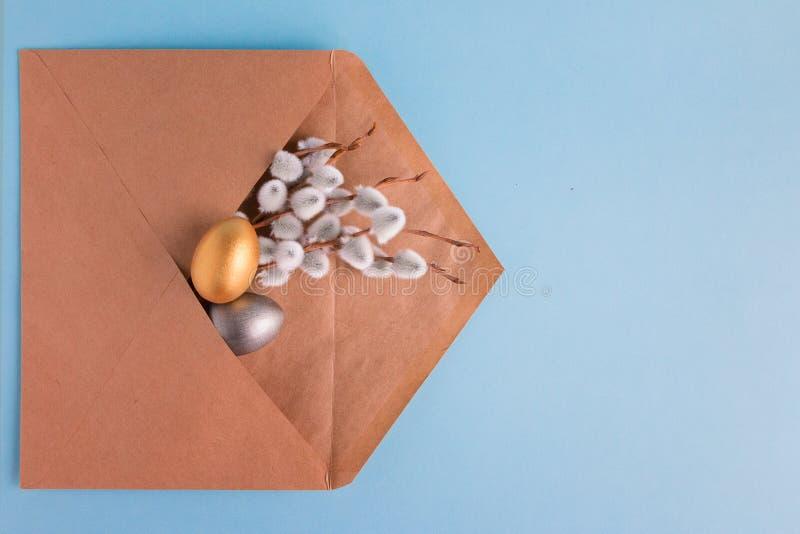 金子和银与一棵杨柳的分支的复活节彩蛋在一个岗位信封的在蓝色背景 r r r 免版税库存照片