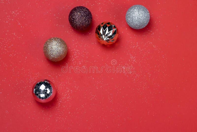金子和银圣诞节装饰在红色纸背景的球 免版税库存图片