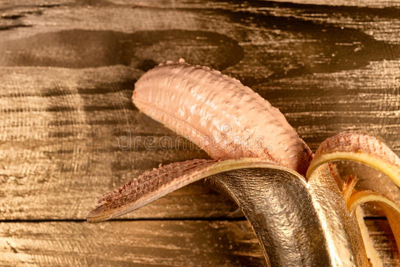 金子在木背景的被剥皮的香蕉 图库摄影