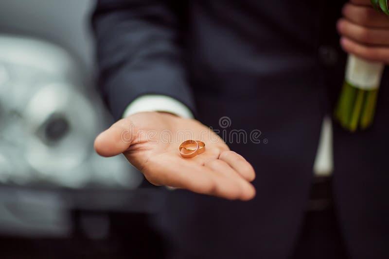金子婚戒在一套衣服的新娘` s手上与花花束  免版税库存图片