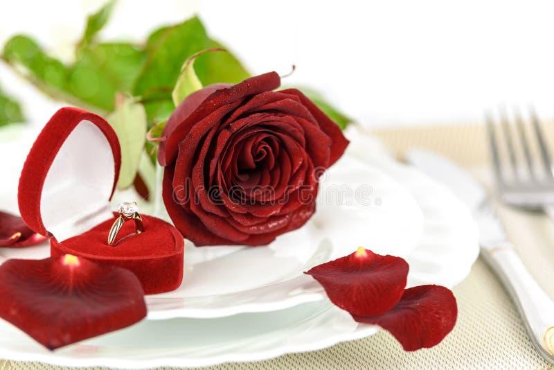 金子定婚戒指和红色玫瑰 库存图片