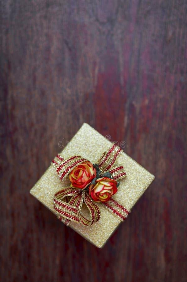 金子颜色有玫瑰纸花的礼物盒 库存照片