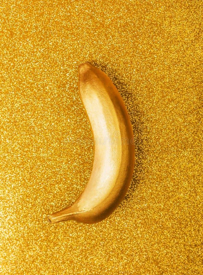 金子颜色食物、金黄香蕉在明亮的闪烁或淡光背景 时髦热带平的位置 r 库存图片